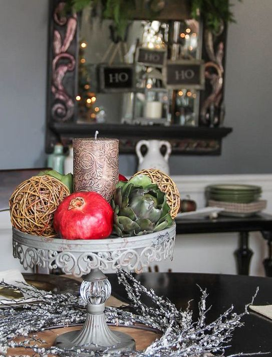 centerpiece with a candle, vine sphere and veggies