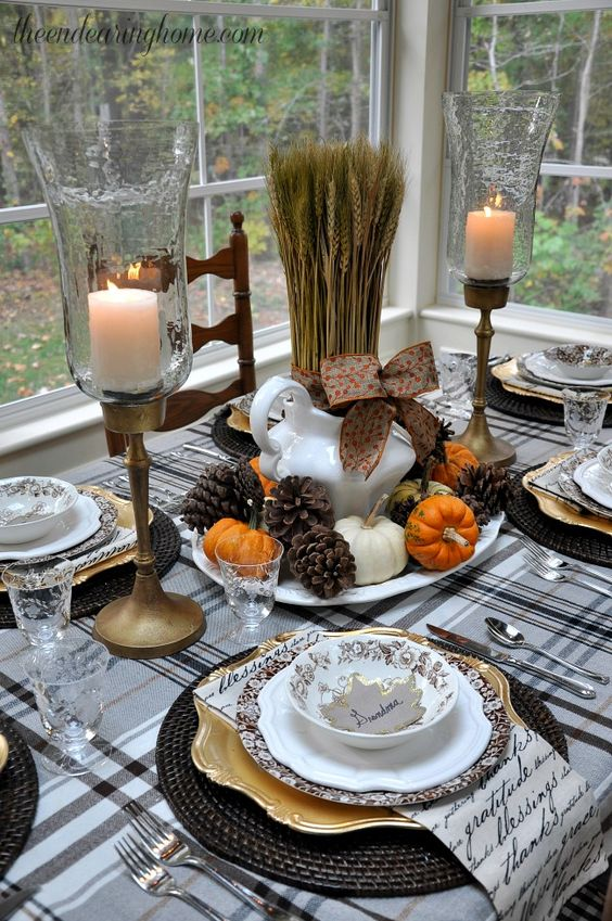 cozy table setting in brown, orange and neutrals with pinecones and wheat