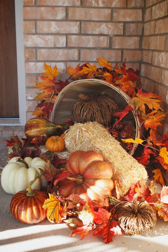 easy pumpkins and hay arrangement in a bucket on a porch - 25 Simple Outdoor Thanksgiving Decorations - Shelterness