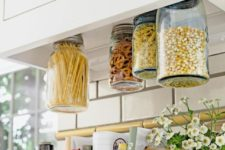 03 add inexpensive mason jars to the bottom of your cabinets for a super clever vertical storage option
