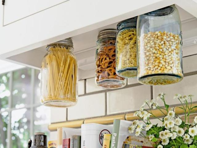 add inexpensive mason jars to the bottom of your cabinets for a super clever vertical storage option