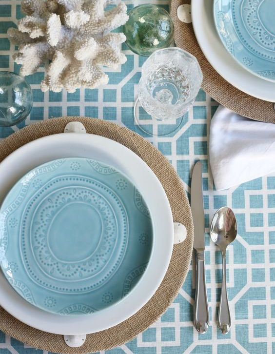 burlap chargers and patterned blue dishes with a croal table runner