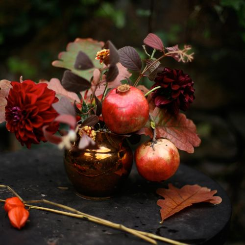 fall arrangement with dark dahlias, leaves and pomegranates