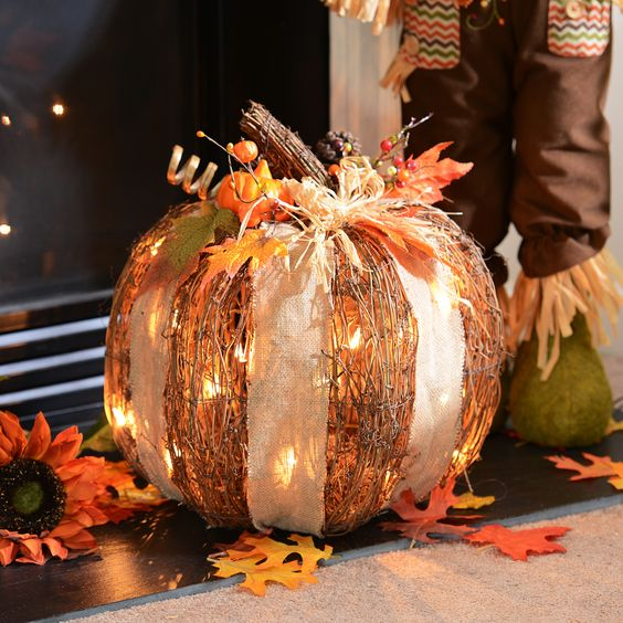 cute rattan pumpkins with white lights and a burlap bow