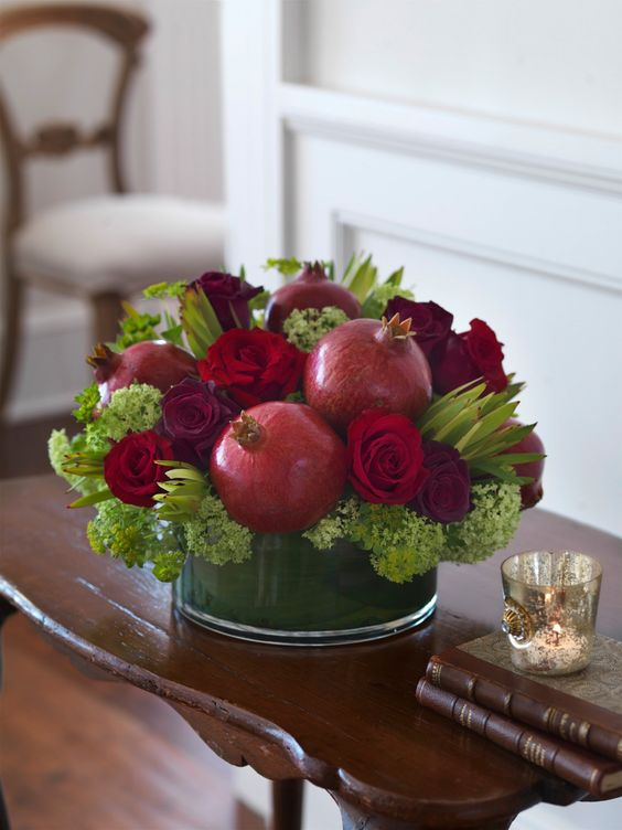 fall arrangement with red roses, greenery and pomegranates