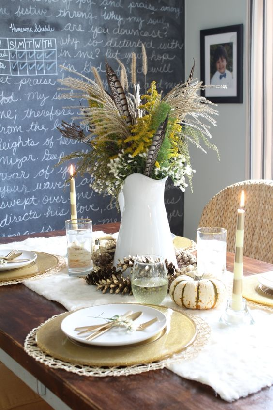 traditional tablescape with gilded pinecones, feathers, greenery and flowers