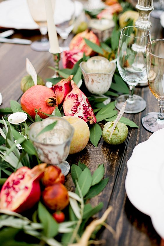 cut pomegranate with greenery and small veggies for table decor