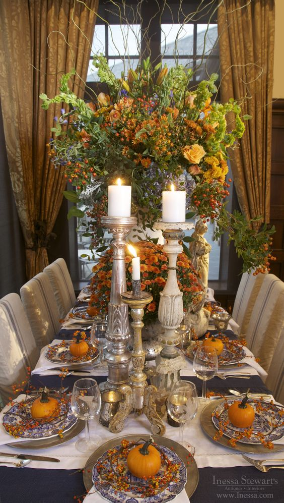 traditional tablescape with lots of orange, pumpkins and candles