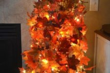 07 make your own fall topiary tree using a tomato cage, fall leaves and lights