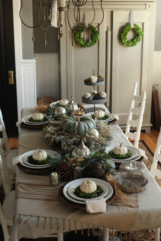 rustic neutral table setting with pumpkins and green wreaths