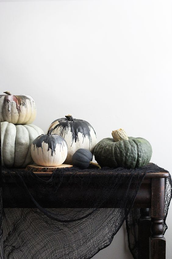 no carve pumpkins on a table with black gauze