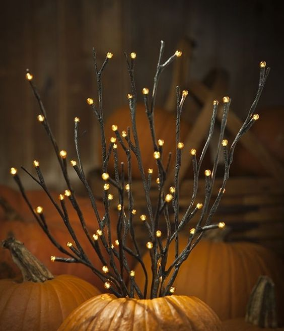 orange LED pre-lit branches placed into pumpkins for fall displays