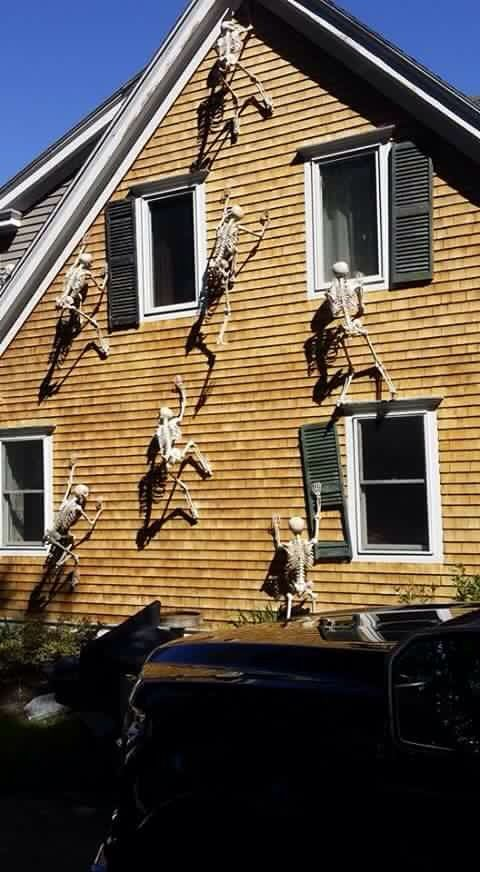 skeletons climbing up the side of the house