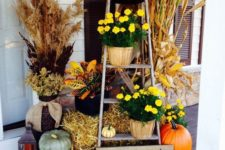 09 yellow potted flowers, hay, pumpkins and a sign