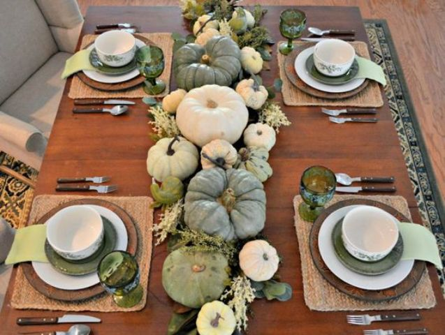 green and white table with a pumpkin table runner and woven placemats