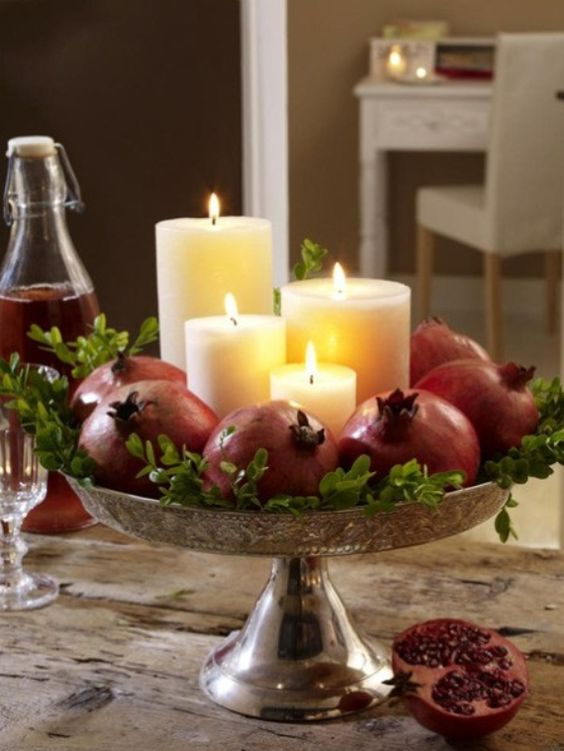 make a stunning fall centerpiece with pillar candles surrounded with pomegranates