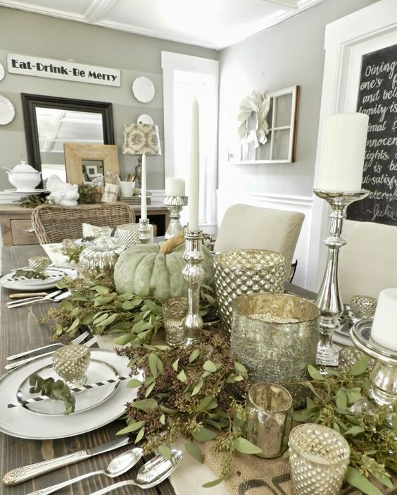 farmhouse-inspired table with silver candle holders, greenery and fresh pumpkins