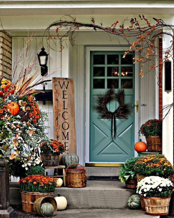 potted seasonal flowers, rich fall arrangement and a rustic sign on the porch