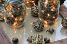 11 use dried moss, acorns, and string lights to craft these rustic lanterns