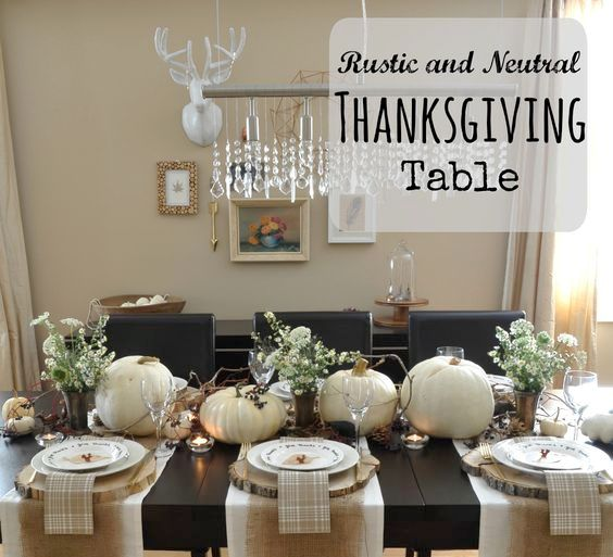 neutral tablescape with white pumpkins and wood slices as chargers