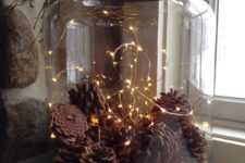 12 tiny lights and pinecones in a jar make a cool fall deocration