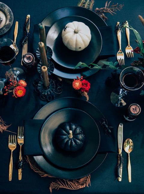 black Halloween table setting with fresh flowers and leaves