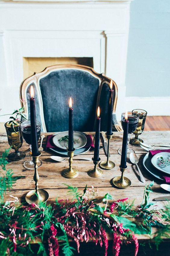 elegant and moody Halloween table with purple flowers and black candles