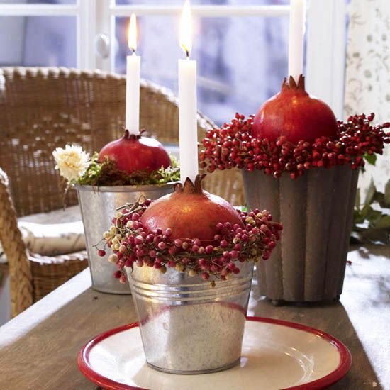 centerpiece in a bucket with berries, pomegranates and candles