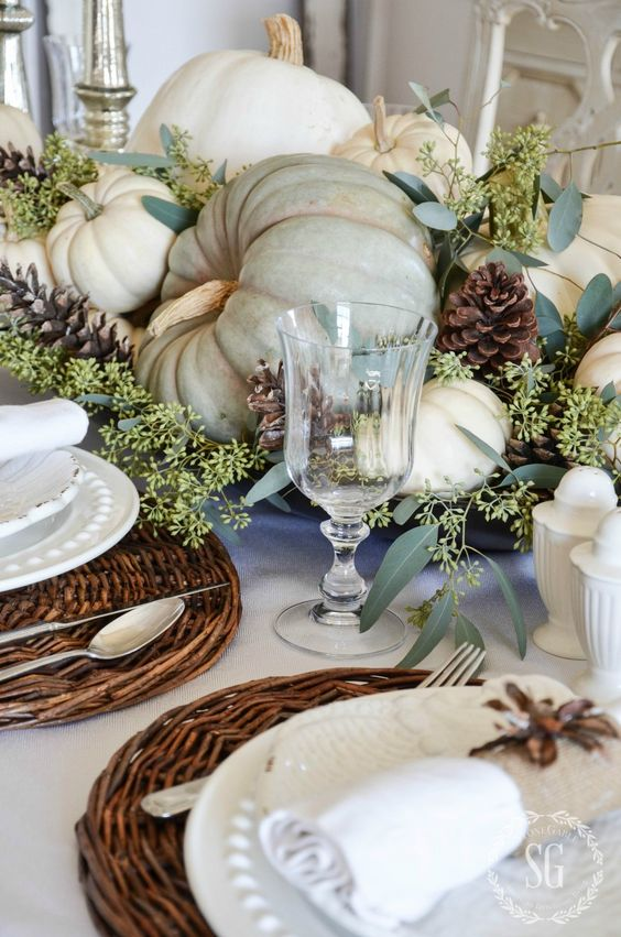 harvest tablescape with pumpkins, pinecones and woven chargers