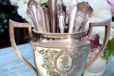 14 mismatched antique teaspoons in an antique silver sugar bowl