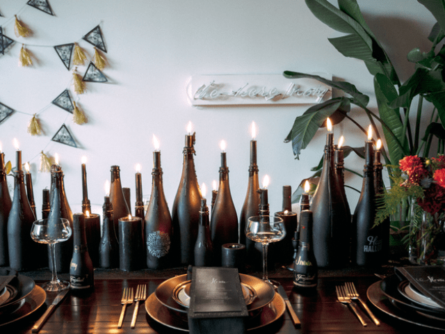 chalkboard bottles used as candle holders create a magical table runner