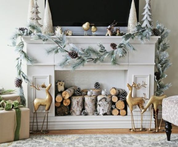 faux fireplace decorated with logs, pinecones and a garland