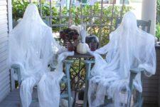 15 foam head muslin ghosts sitting on a porch