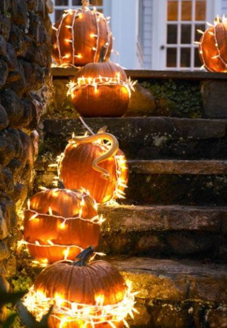 brighten your traditional outdoor fall decor by simply wrapping pumpkins in string lights
