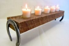 16 candle holder made of a couple of horseshoes and a thick board