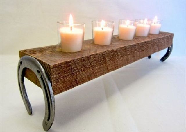 candle holder made of a couple of horseshoes and a thick board