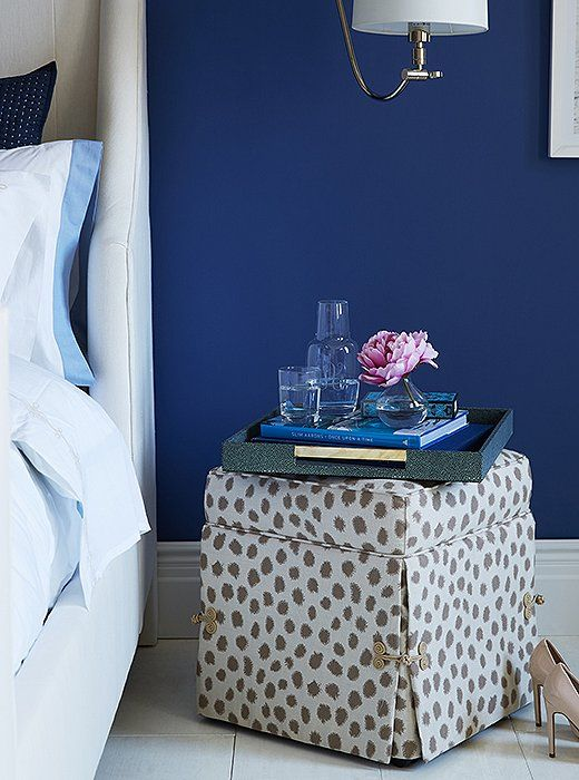 a skirted ottoman topped with a shagreen tray makes for a fun, unfussy nightstand alternative