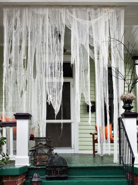 cheesecloth for imitating spiderweb is an amazing front porch decoration