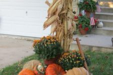 17 faux pumpkins and potted flowers displayed on a wooden trolley and corn husks