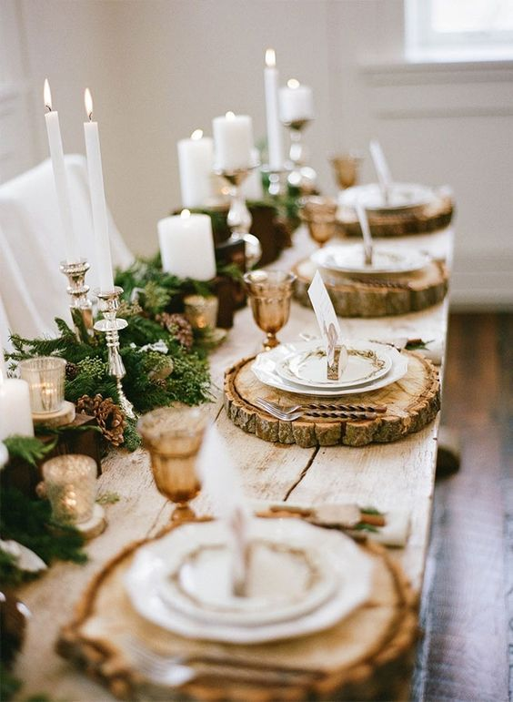 rustic yet elegant table setting with fir, pinecones, candles and wood slices as chargers