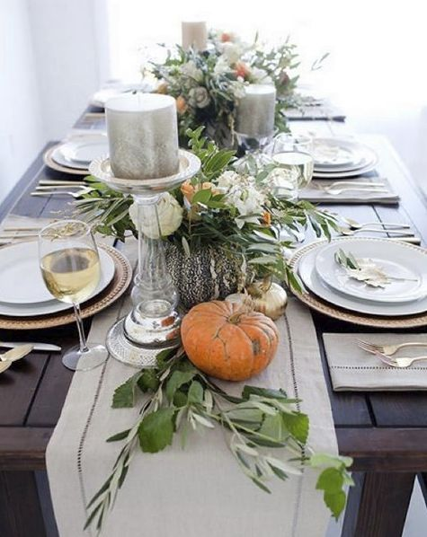 Modern Table Decor With A Table Runner Of Pumpkins, Candles And Greenery