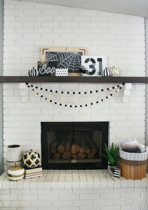 black and white mantel with printable art, pumpkins and spider web