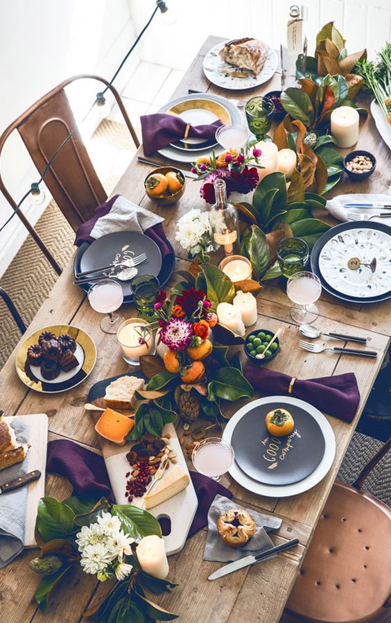 bold tablescape with leaves, fruit and flowers and purple napkins