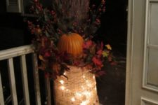 21 lights in a burlap sack, which contains a bold fall arrangement