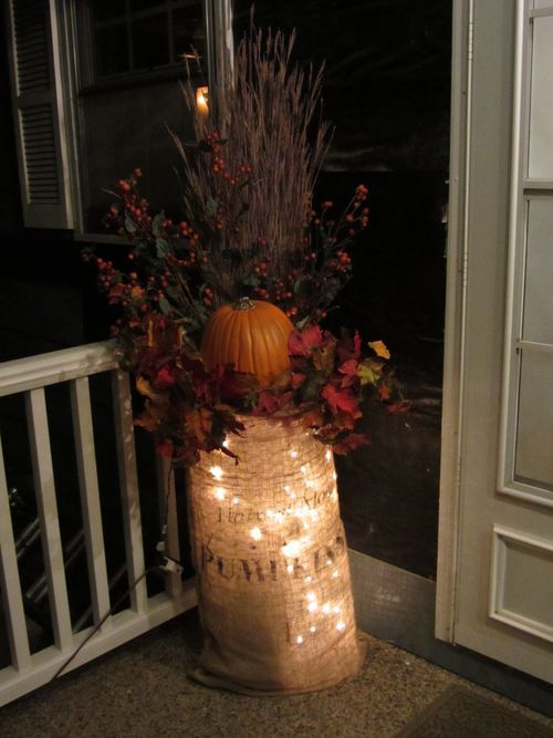 lights in a burlap sack, which contains a bold fall arrangement