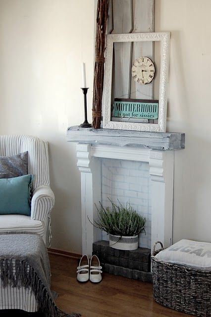 tiny whitewashed fireplace with potted greenery inside