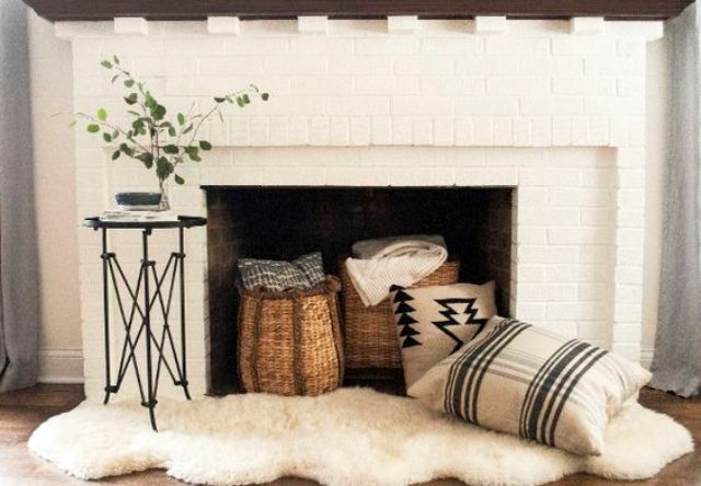 cozy up your fireplace with pillows, baskets and blankets