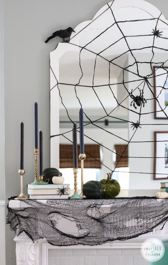 modern Halloween mantle with its spider web mirror, ravens and gold candle sticks