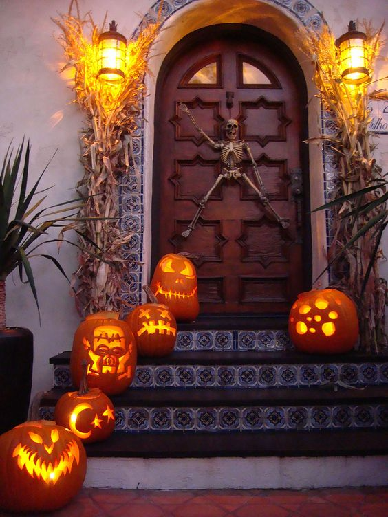 skeleton door decor and carved pumpkins on the stairs