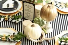 23 modern table setting with a striped tablecloth, natural pumpkins, antlers and feathers